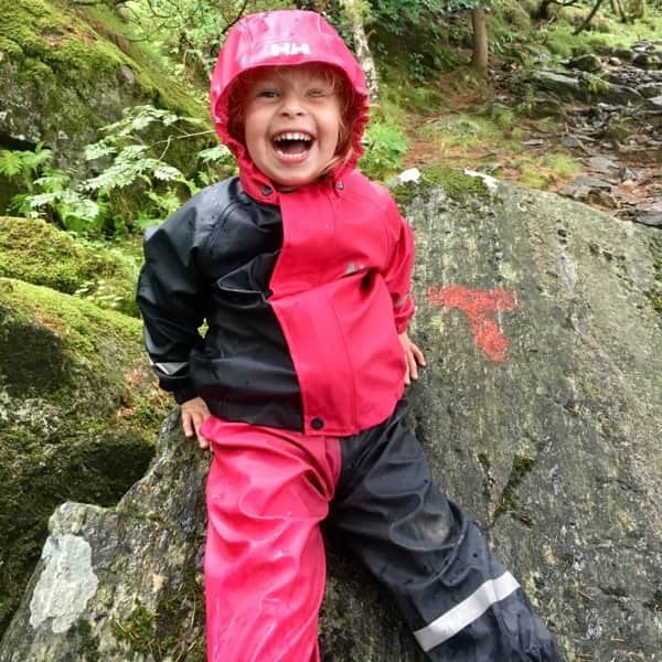 Picture of a small girl in rain clothes. She's sitting in the forest smiling, even if it rains.